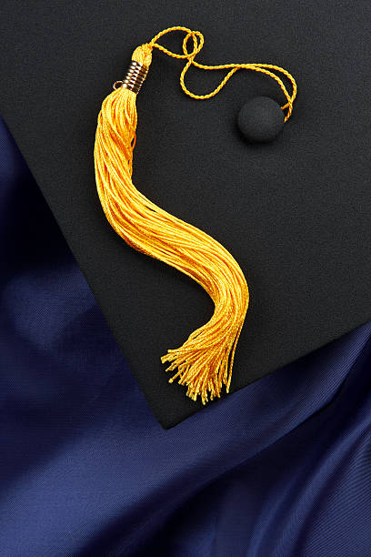 Black mortarboard, blue gown, yellow tassel Black mortarboard with yellow tassel shot on blue graduation gown, space for copy tassel stock pictures, royalty-free photos & images