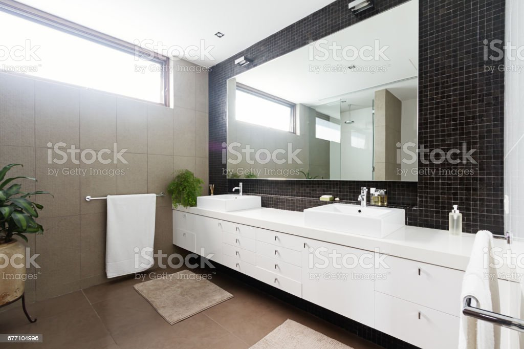 Black mosaic tiled splashback and double basin bathroom stock photo