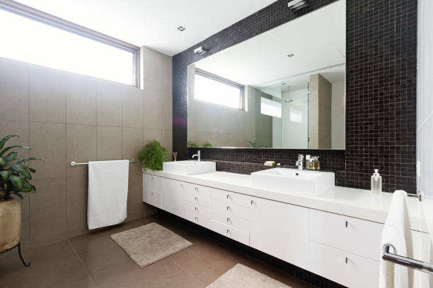 black mosaic tiled splashback and double basin bathroom - bathroom renovation stock photos and pictures