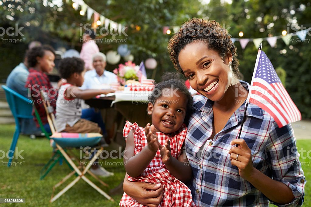 Black mother and baby hold flag at 4th July party, stock photo