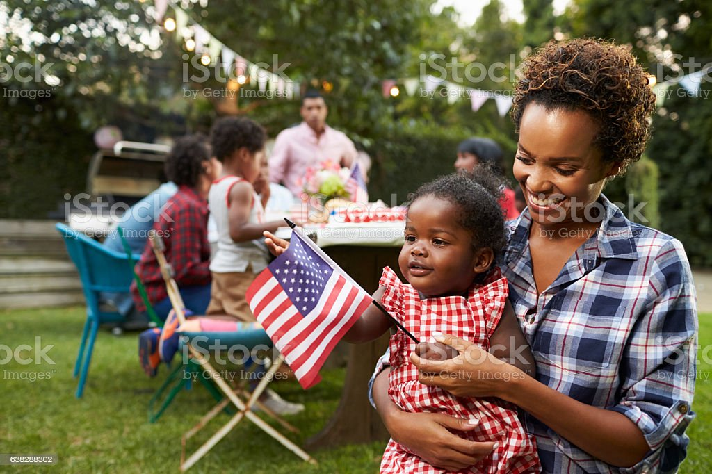 Black mother and baby holding flag at 4th July garden stock photo