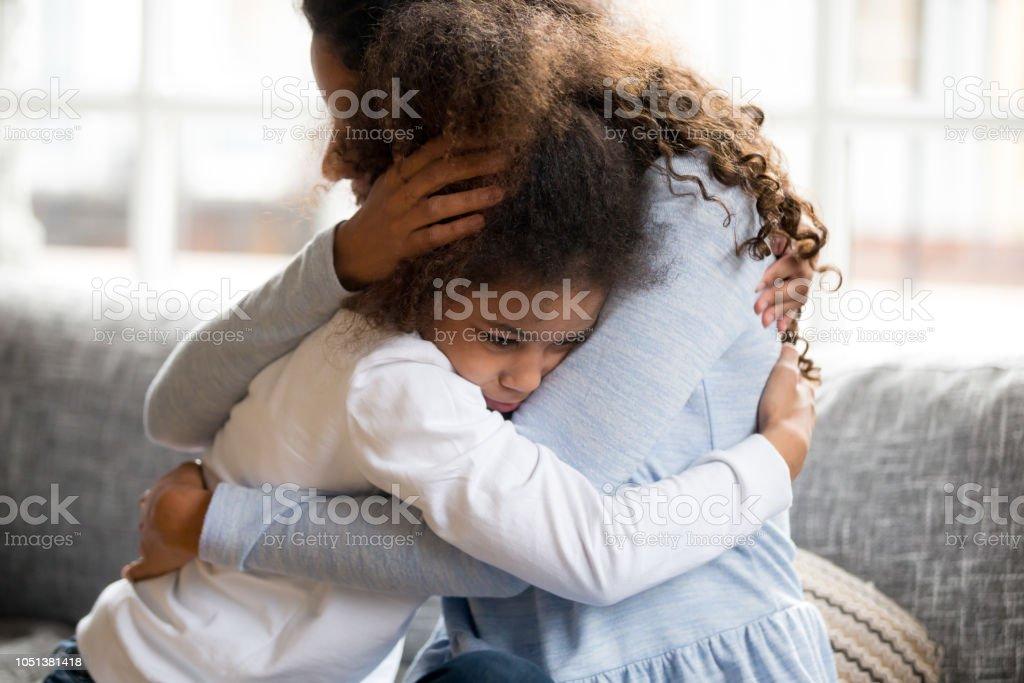 Svart mor och dotter embracing sitter på soffan - Royaltyfri Afrikanskt ursprung Bildbanksbilder
