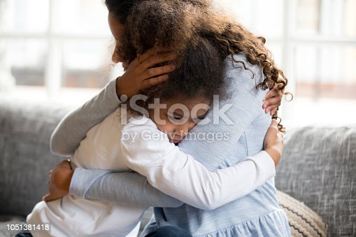 istock Black mother and daughter embracing sitting on couch 1051381418