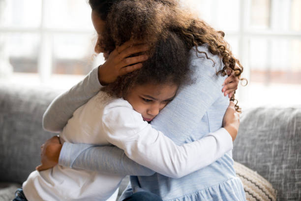 black mother and daughter embracing sitting on couch - comfort stock photos and pictures