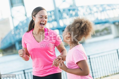 A black woman in her 30s standing outdoors by the waterfront in a city, laughing with her 7 year old daughter. They are wearing pink t-shirts, holding hands.