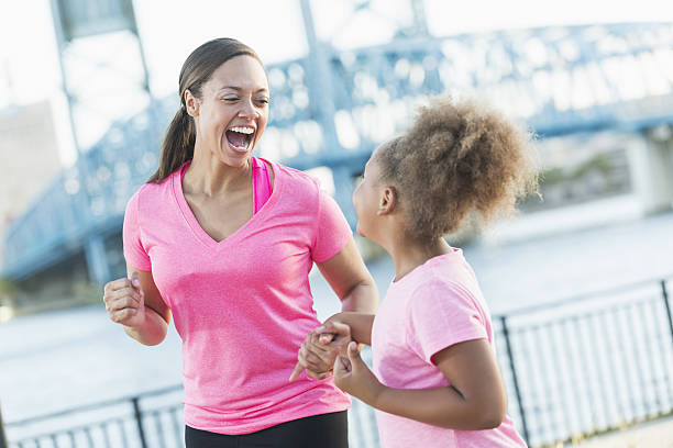 black mother and daughter holding hands,  laughing - rosa training stock-fotos und bilder