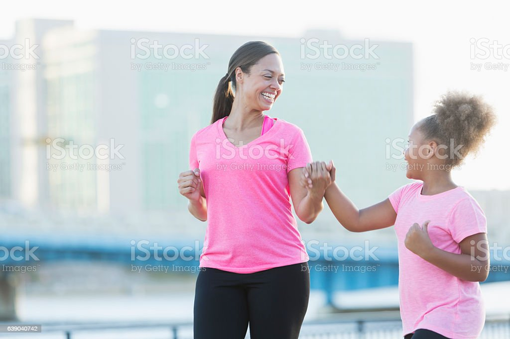 Black mother and daughter walking, holding hands, exercising stock photo