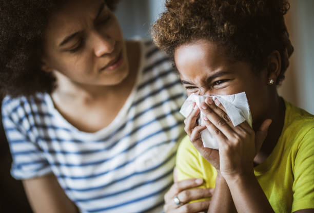 Black mother consoling her daughter who is blowing a nose. Ill African American girl blowing a nose at home while her mother is consoling her. allergy stock pictures, royalty-free photos & images