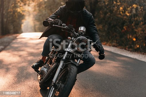 Handsome biker with classic style black motorcycle. Cafe racer