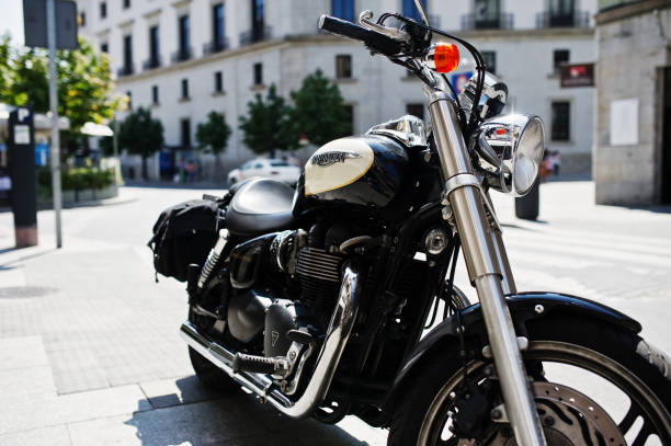 black motorcycle triumph on the street of a town. - triumph foto e immagini stock