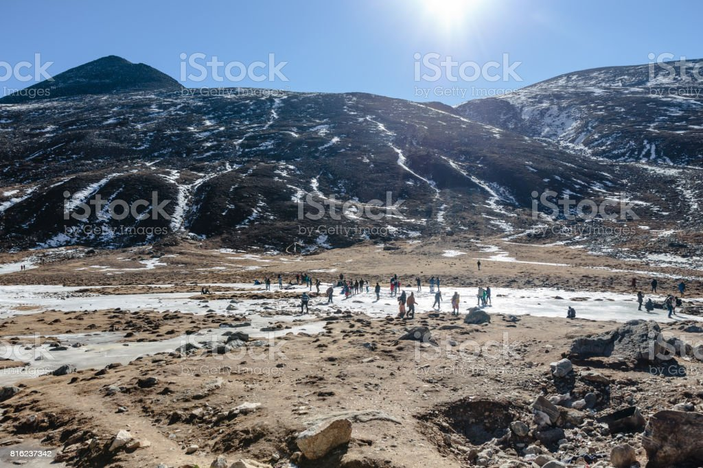 Black mountain witn snow and below with tourists on the ground with brown grass, snow and frozen pond in winter at Zero Point at Lachung. North Sikkim, India. stock photo