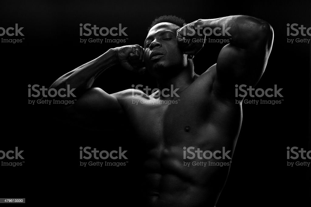 Black muscled male posing with raised arms stock photo
