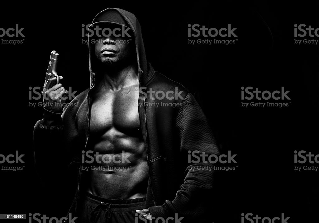 black muscled man wearing hoody holding a gun stock photo
