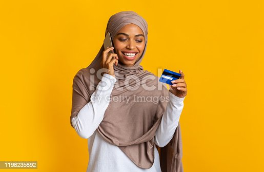 1173546354 istock photo Black muslim woman holding credit card and talking on cellphone 1198235892