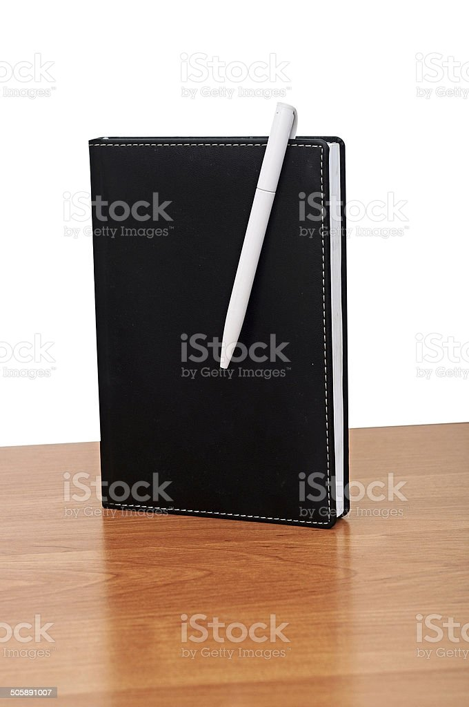 Black notepad and pen on table stock photo