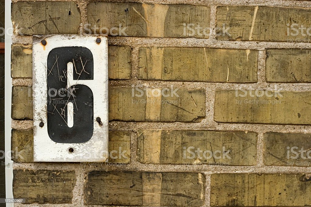Black number 6 posted on white on a rough brick wall royalty-free stock photo