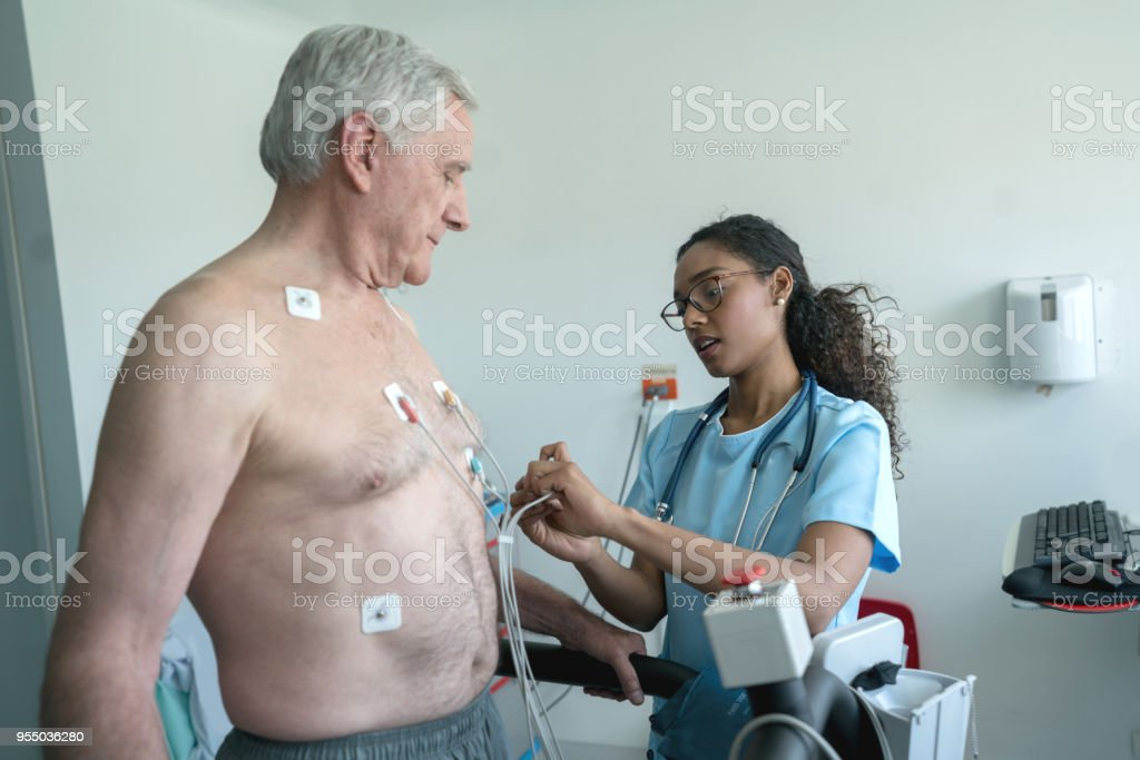 Enfermeira negra colocando electrones num paciente sênior que está pronto para um teste de esforço em esteira - foto de acervo