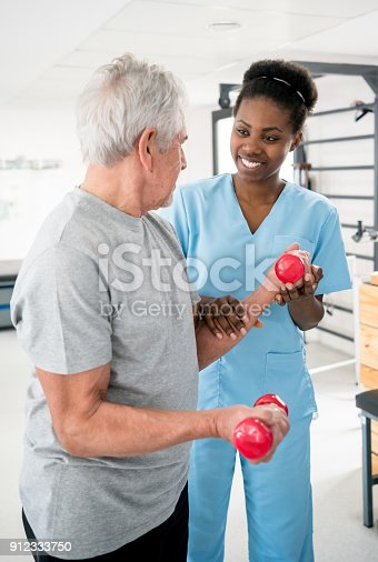 istock Black occupational therapist helping a senior patient with his free weights workout 912333750