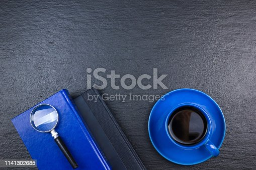 615494694 istock photo Black Office desk table with computer, pen and a cup of coffee, lot of things. Top view with copy space. 1141302685