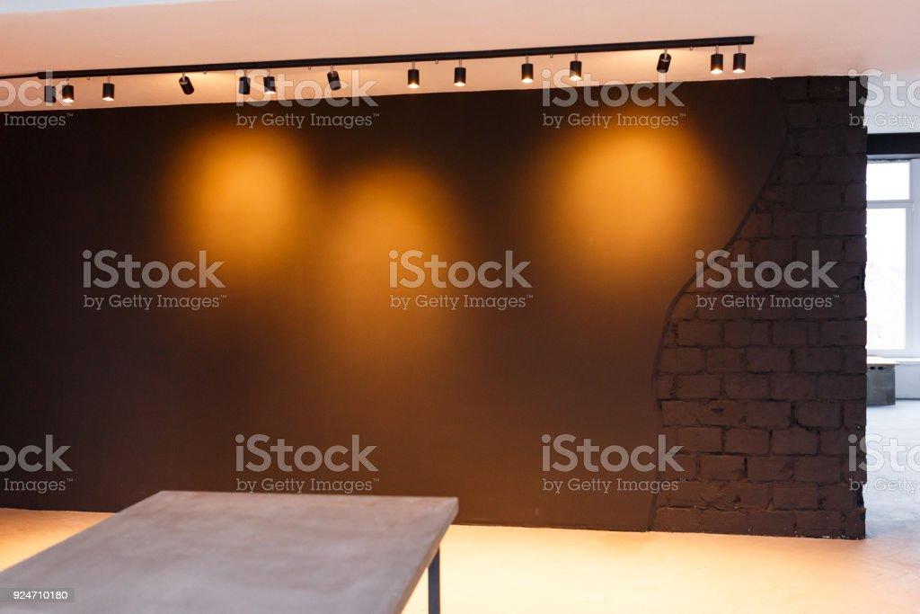 Mur de bureau noir avec spot de lumière sur style loft table en