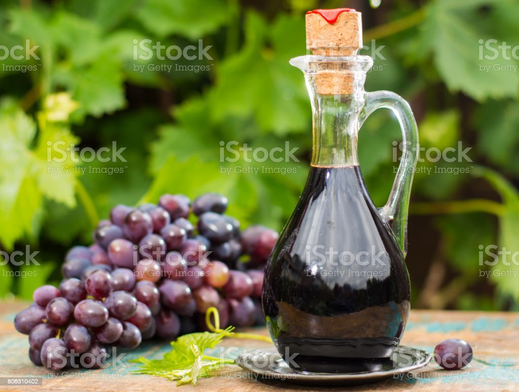 Black old balsamic vinegar in a glass jug with fresh red grapes on green vineyard background stock photo
