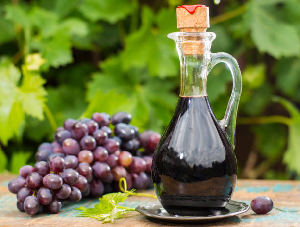 Black old balsamic vinegar in a glass jug with fresh red grapes on green vineyard background Black old balsamic vinegar in a glass jug with fresh red grapes on green vineyard background on wooden table, outside balsamic vinegar stock pictures, royalty-free photos & images