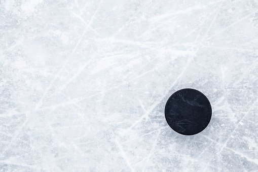 Black old rubber puck on ice background. Closeup. Empty place for text. Top down view.