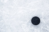 istock Black old rubber puck on ice background. Closeup. Empty place for text. Top down view. 1301550691