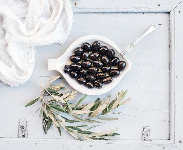 Black olives in white ceramic plate with tree branches, top​​​ foto