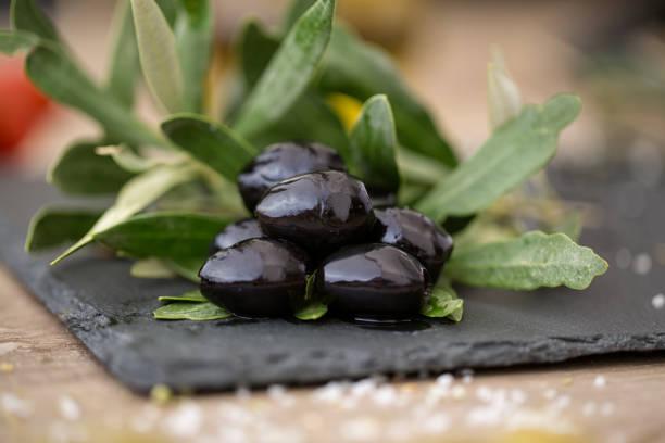 schwarze oliven auf natürliche olivenbaum blätter - schwarze olive stock-fotos und bilder