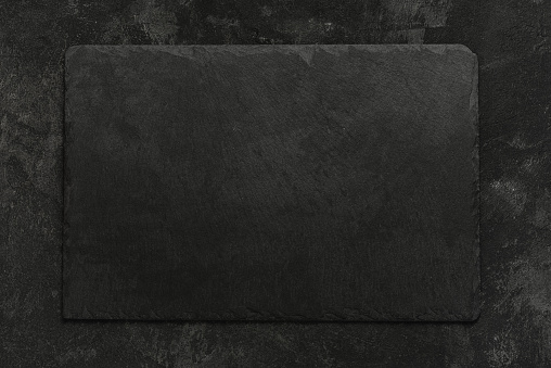 Black on black. Empty black granite stone rectangle board on black textured cement background, top view vith copy space for your text.