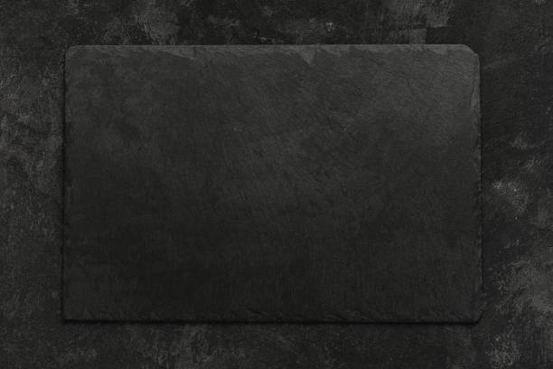 Black on black. Empty black granite stone rectangle board on black textured cement background, top view vith copy space for your text. stock photo