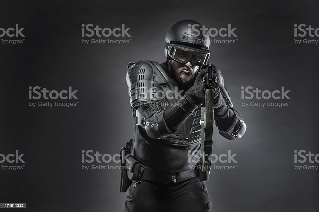Wartime soldier with full bullet proof body armor holding an assault...