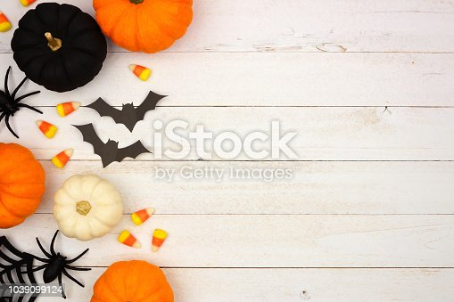 istock Black, orange and white Halloween side border over white wood 1039099124