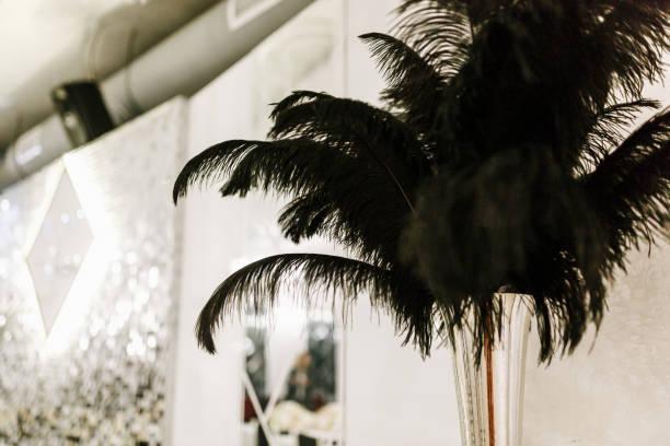 schwarzen straußenfedern in schwarzer vase, hochzeit dekoration details - hochzeits thema hollywood stock-fotos und bilder