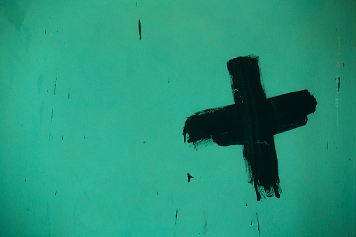 Black paint brush texture cross mark on a green concrete wall background