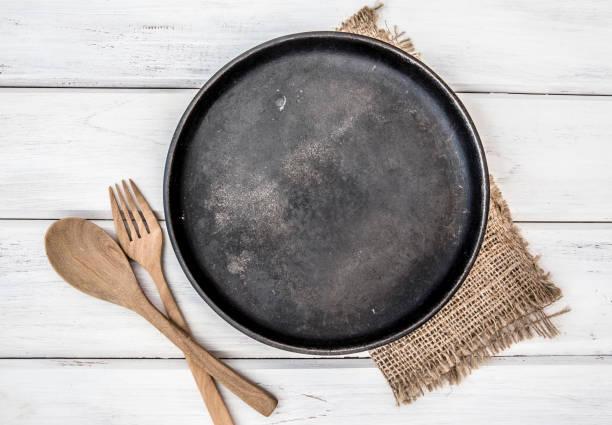 Schwarzes Pfanne Brett und ein Tischtuch mit Holzgabel und Löffel auf weißem Tisch, Rezepte Lebensmittel für gesunde Gewohnheiten erschossen Note Hintergrundkonzept – Foto