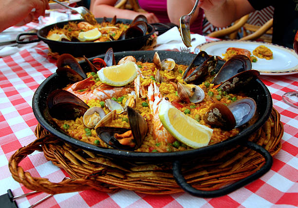 A black pan of paella on a checkered tablecloth Spanish paella with seafood in a pan catalonia stock pictures, royalty-free photos & images