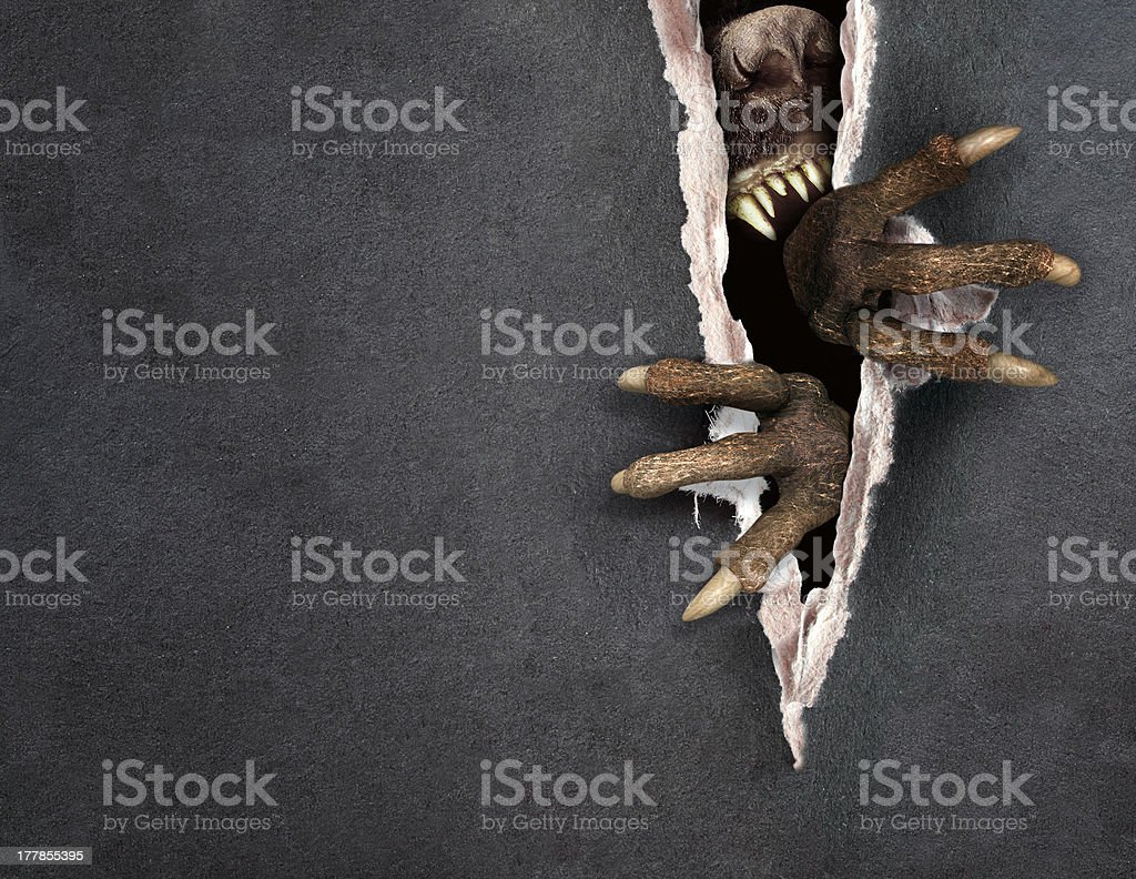 Black paper being torn apart by a monster stock photo