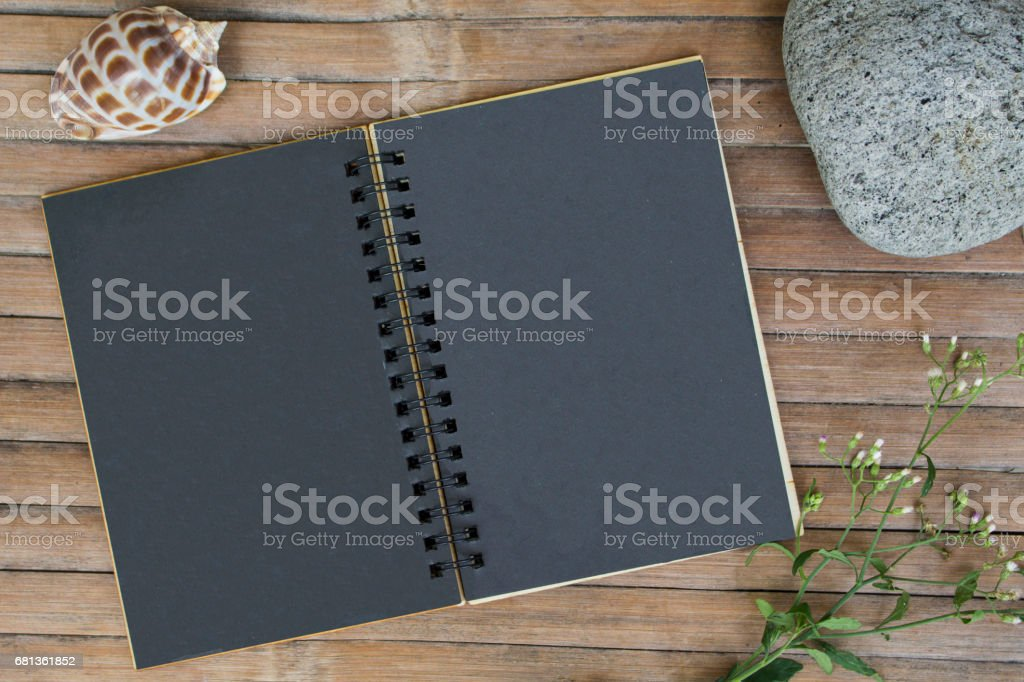 Black paper notebook on rustic wooden background with natural decor....