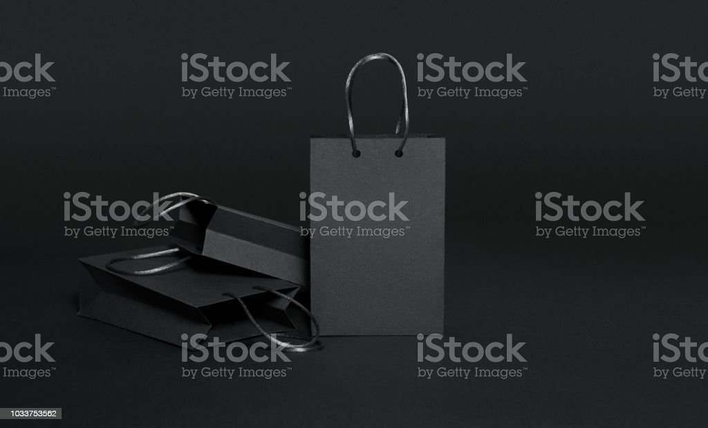 Black paper shopping bags on black background stock photo