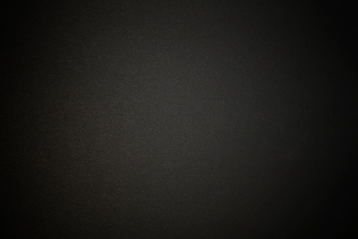 Close-up of a black paper texture background with spotlight.