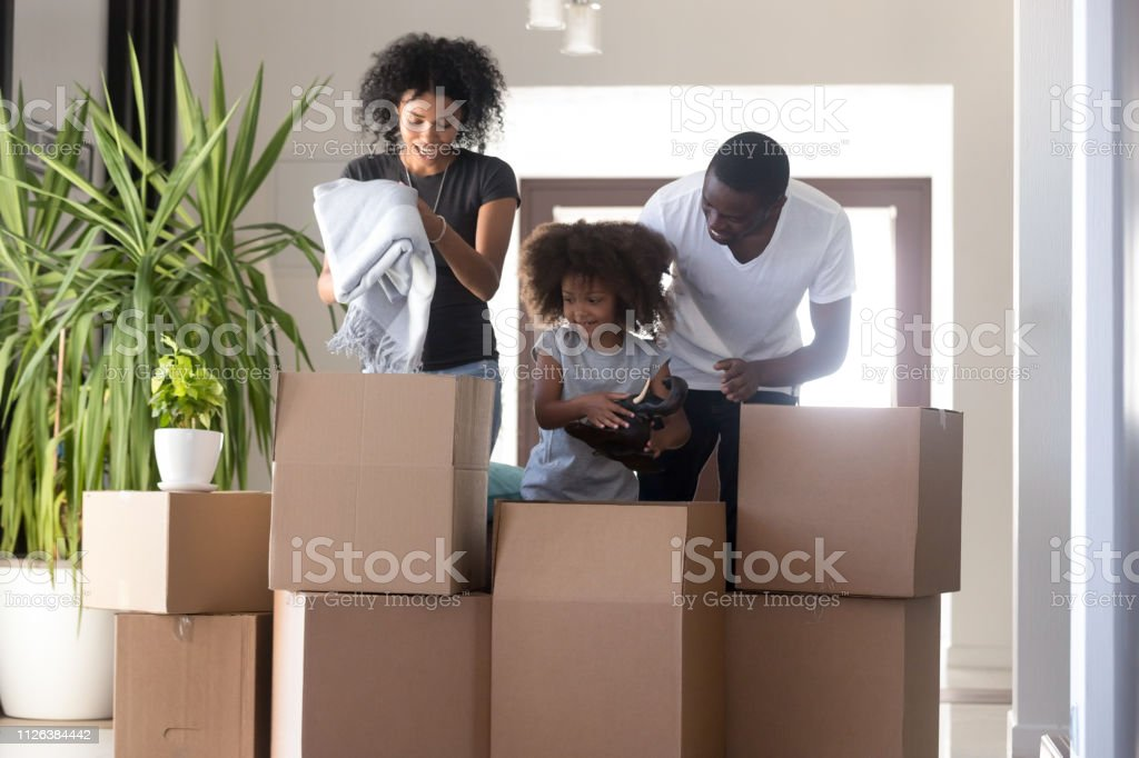 African american family having fun unpacking boxes with kid helping...