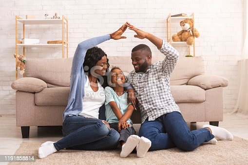 Family care and protection. Black parents making symbolic roof of hands above their little daughter's head, sitting together on floor at home