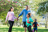 A black couple walking in the park, holding hands. Their two young children are playing, running around them. They are looking toward their 7 year old daughter who is holding a ball.