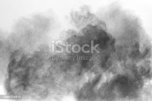 istock Black particles splattered on white background. Black powder dust splashing. 1085274312