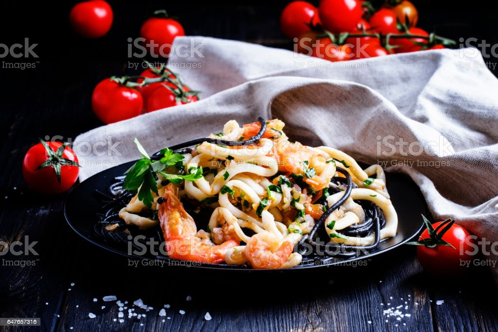 Black pasta with seafood and tomato sauce on a plate stock photo