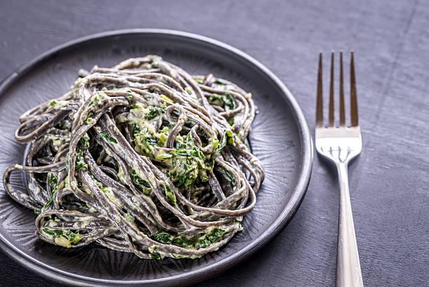 black pasta mit spinat-mascarpone, parmesan - spaghetti mit spinat stock-fotos und bilder