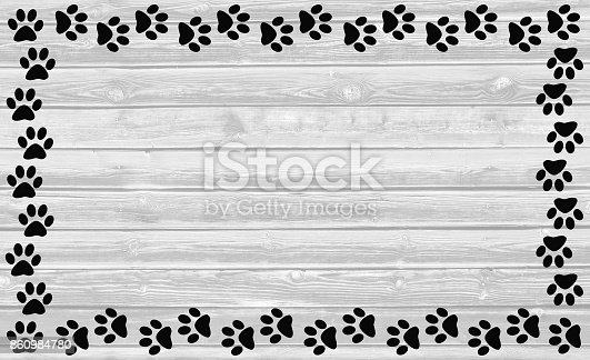 istock Black paw prints frame on white wooden background. 860984780