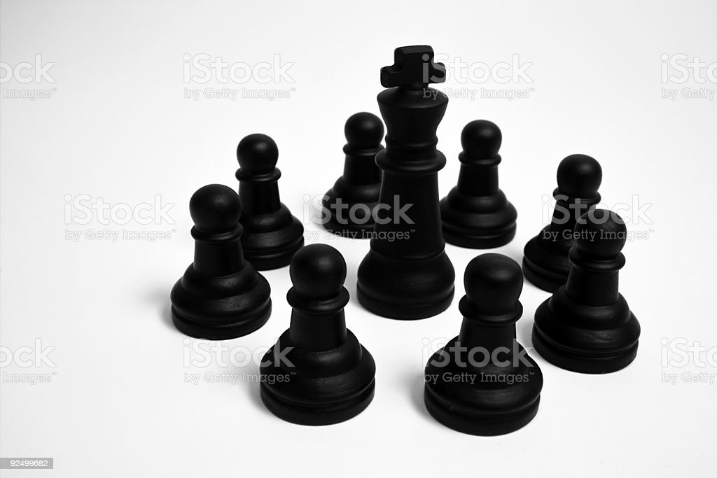 Black pawns and the king stock photo